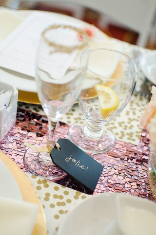 wedding-shower-black-place-cards-with-names-in-gold-ink-tied-with-gold-ribbon-to-champagne-flute