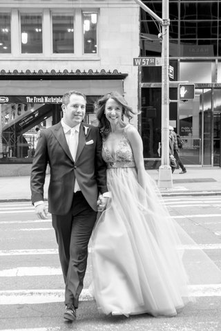 black-and-white-photo-of-couple-running-streets-of-new-york-city-wedding-dress-suit-crosswalk