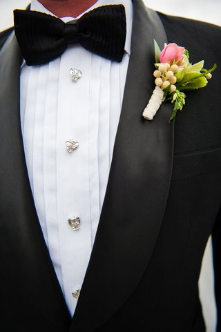 groom-in-tuxedo-with-silver-buttons-and-black-bow-tie-textured-boutonniere-pink-flower