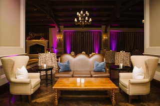 wedding-lounge-area-next-to-dance-floor-purple-uplighting-on-curtains-plush-furniture-and-pillows