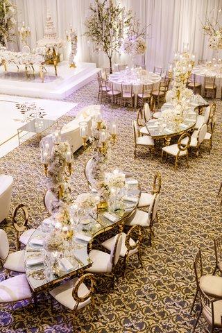 wedding-reception-ballroom-tahir-whitehead-mirror-serpentine-table-gold-chairs-tall-centerpieces