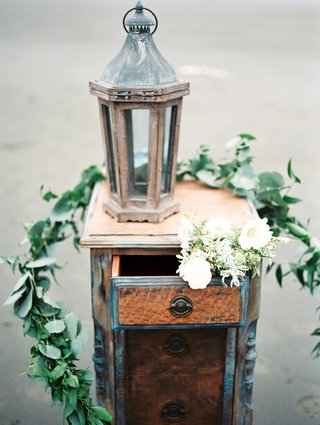 an-old-antique-dresser-with-a-chipped-lantern-white-bouquet-and-green-garland-of-leaves