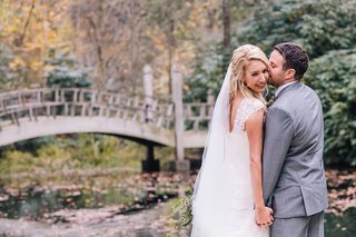 grooms-kisses-his-bride-on-the-cheek-as-they-stand-outside-near-a-lake-with-a-bridge