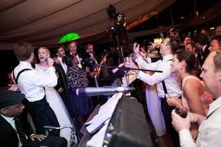 a-fun-loving-bride-and-groom-join-their-reception-band-onstage-to-sing-a-song