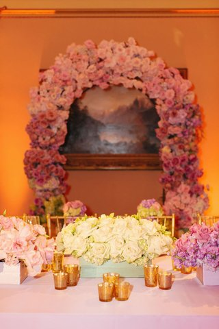 single-variety-bouquets-in-low-boxes-and-pink-ombre-arch-on-wall