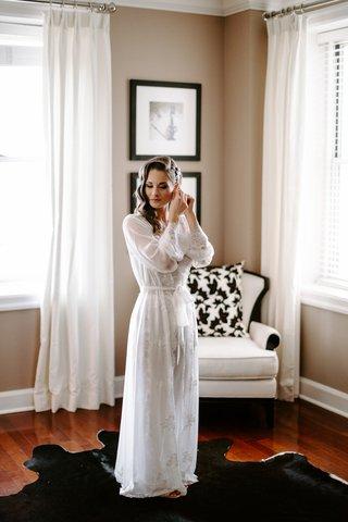 bride-with-curled-wedding-hair-in-bridal-suite-black-cowhide-rug-white-long-sleeve-sheer-robe-gown