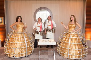 servers-in-gold-ball-gowns-with-metal-champagne-holders-on-skirts-and-oyster-shucker-servers