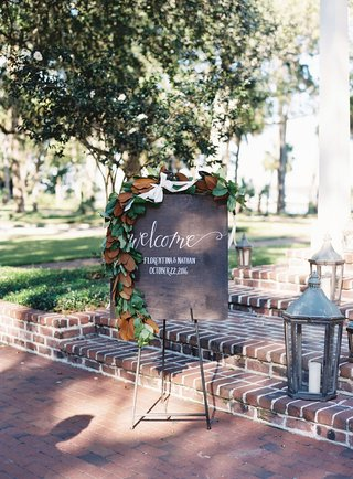 wood-welcome-sign-with-calligraphy-wrought-iron-lanterns-on-brick-stairs-magnolia-leaves-garland