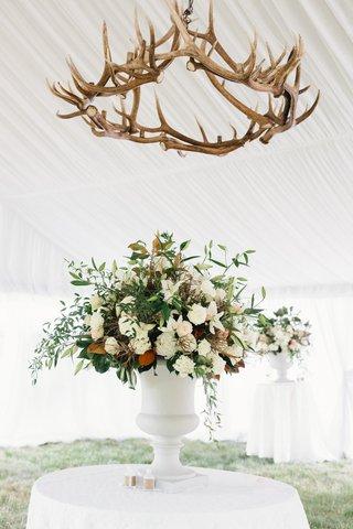 white-tent-with-flower-arrangement-green-leaves-white-flowers-antler-chandelier-overhead