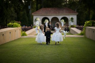 back-view-of-two-flower-girls-holding-hands-of-toddler-ring-bearer-in-the-middle