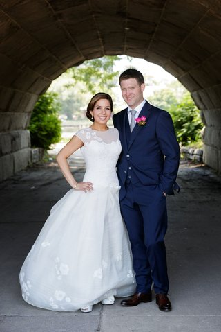bride-in-cap-sleeve-drop-waist-wedding-dress-with-groom-in-navy-blue-suit-and-tie