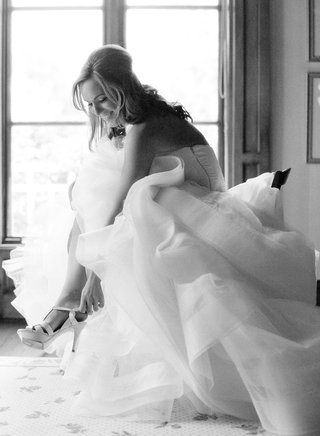 black-and-white-photo-of-bride-in-vera-wang-wedding-dress-putting-on-high-heel-shoes