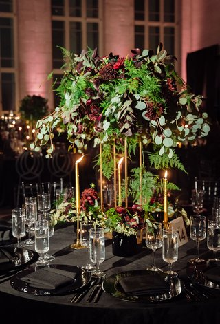 tall-centerpiece-of-unstructured-greenery-and-oxblood-flowers-tall-taper-candles-in-gold-black-linen