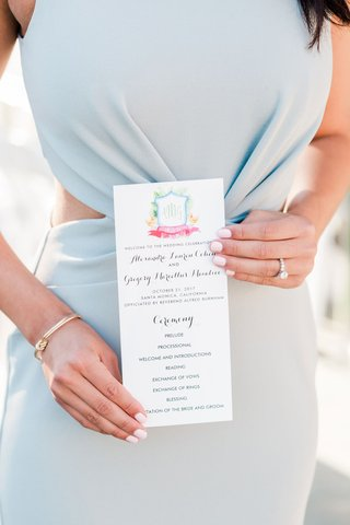 wedding-guest-in-light-blue-dress-with-side-cutouts-holding-wedding-ceremony-program-tropical-crest