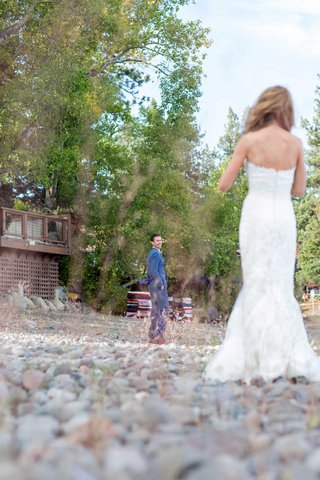 groom-turns-around-to-see-his-bride-during-first-look-blue-suit-white-dress-pebbles-forest