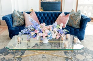 blue-tufted-velvet-sofa-with-pink-pillows-pink-and-blue-floral-arrangement-wedding-lounge-area