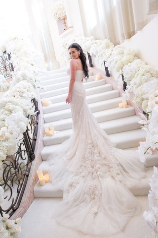 bride-in-inbal-dror-wedding-dress-with-dramatic-embellished-train-on-stairs-covered-in-flowers