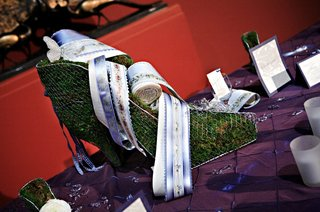 metal-shoe-mold-filled-with-grass-and-decorated-with-floral-ribbons-and-butterfly-applique