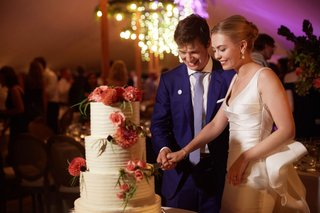 wedding-photo-of-bride-and-groom-cutting-into-white-buttercream-wedding-cake-decorated-pink-flowers