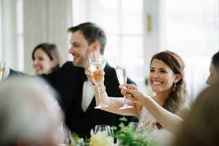 wedding-reception-long-reception-tables-toasting-champagne-glasses-flutes-in-air