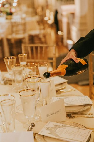 wedding-reception-gold-white-table-with-gold-rim-glassware-flute-filling-up-with-champagne
