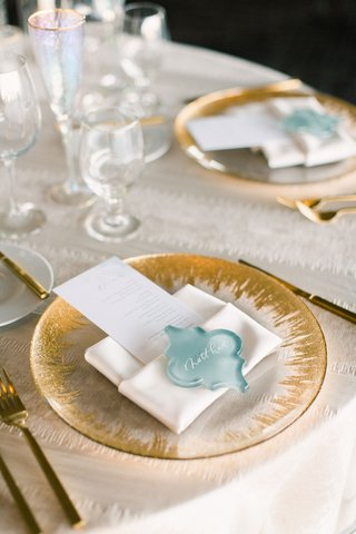wedding-reception-place-setting-with-decorative-sea-glass-as-place-cards-on-gold-detailed-charger