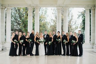 bride-in-berta-wedding-dress-groom-with-bridesmaids-in-black-evening-gowns-groomsmen-in-tuxedos