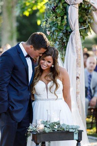 bride-in-strapless-wedding-dress-crystal-belt-sash-groom-in-navy-blue-suit-with-marsala-bow-tie