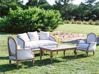 wedding-reception-upholstered-rental-furniture-on-lawn-with-wood-coffee-table-yellow-flowers-lounge