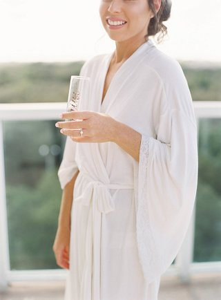 bride-in-white-robe-with-engagement-ring-holding-champagne-flute-with-gold-calligraphy