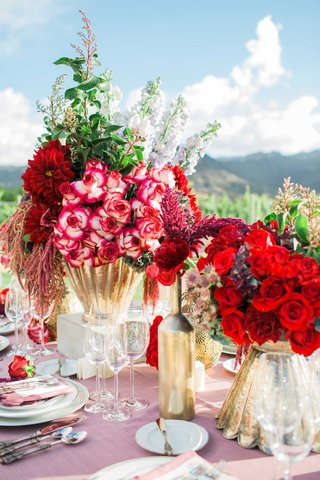 red-and-dark-purple-flower-floral-arrangements-in-gold-vases-with-pink-table-linens-vineyard-setting