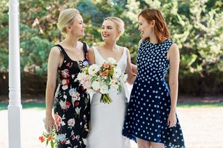 bride-in-classic-wedding-dress-with-mother-of-bride-in-flower-print-dress-and-sister-in-blue-dress