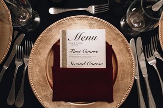 wedding-reception-menu-with-gold-glitter-border-on-side-placed-in-burgundy-napkin-on-gold-charger