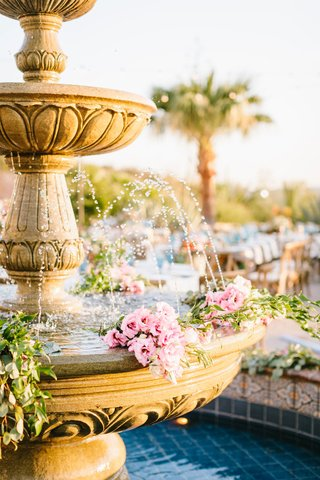 wedding-reception-outdoor-courtyard-reception-palm-tree-stone-fountain-with-pink-flowers-greenery