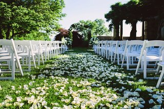outdoor-wedding-ceremony-on-grass-lawn-white-flower-petals-white-chairs-and-greenery-arch