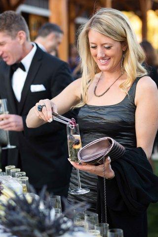 wedding-guest-adding-raspberry-blackberry-and-peach-to-champagne-flute-garnish