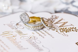 yellow-gold-wedding-rings-stack-halo-engagement-ring-sparkling-on-white-gold-wedding-invitation