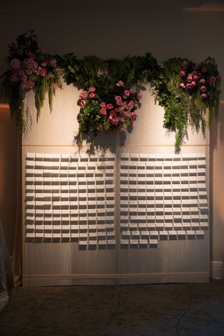 wedding-reception-cocktail-hour-escort-card-display-wall-pink-roses-greenery-on-top