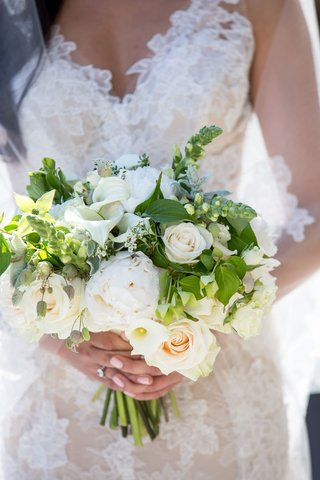 bride-in-monique-lhuillier-lace-wedding-dress-holding-bouquet-with-white-rose-calla-lily-and-peony
