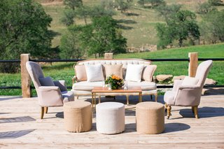 tan-white-ivory-pouf-ottoman-armchair-sofa-pillows-coffee-table-wedding-lounge-for-cocktail-hour