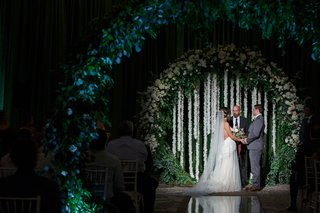 wedding-ceremony-bride-and-groom-flower-circle-arch-cascading-white-flowers-greenery-lighting