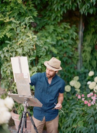 destination-wedding-entertainment-idea-live-painter-painting-the-ceremony-fedora-hat