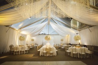 tented-wedding-reception-with-white-draping-floral-arrangements-linens-gold-chairs
