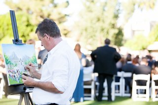 man-in-white-shirt-paints-alfresco-wedding