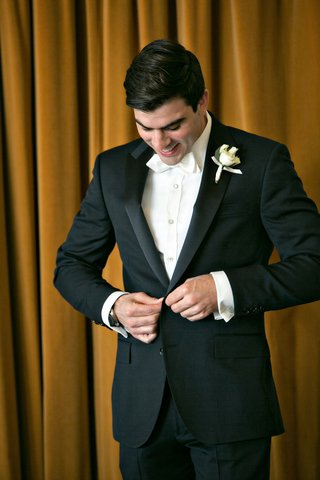 black-tuxedo-and-white-collar-bow-tie-buttons-boutonniere-buttoning-jacket