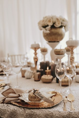 fall-wedding-ideas-pumpkin-with-place-card-ribbon-gold-charger-flatware-pumpkin-centerpiece-candles