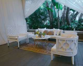 wedding-lounge-area-with-white-sofa-chairs-gold-marble-coffee-table-persian-rug
