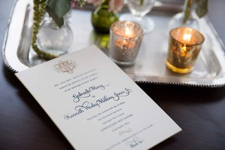 white-wedding-invitation-with-blue-calligraphy-and-a-gold-monogram