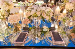 mirror-wedding-reception-table-with-clusters-of-white-flowers-and-candlelight-evening-rooftop-dinner