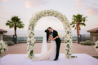 outdoor-wedding-ceremony-bride-and-groom-kissing-galia-lahav-dress-white-flowers-palm-trees